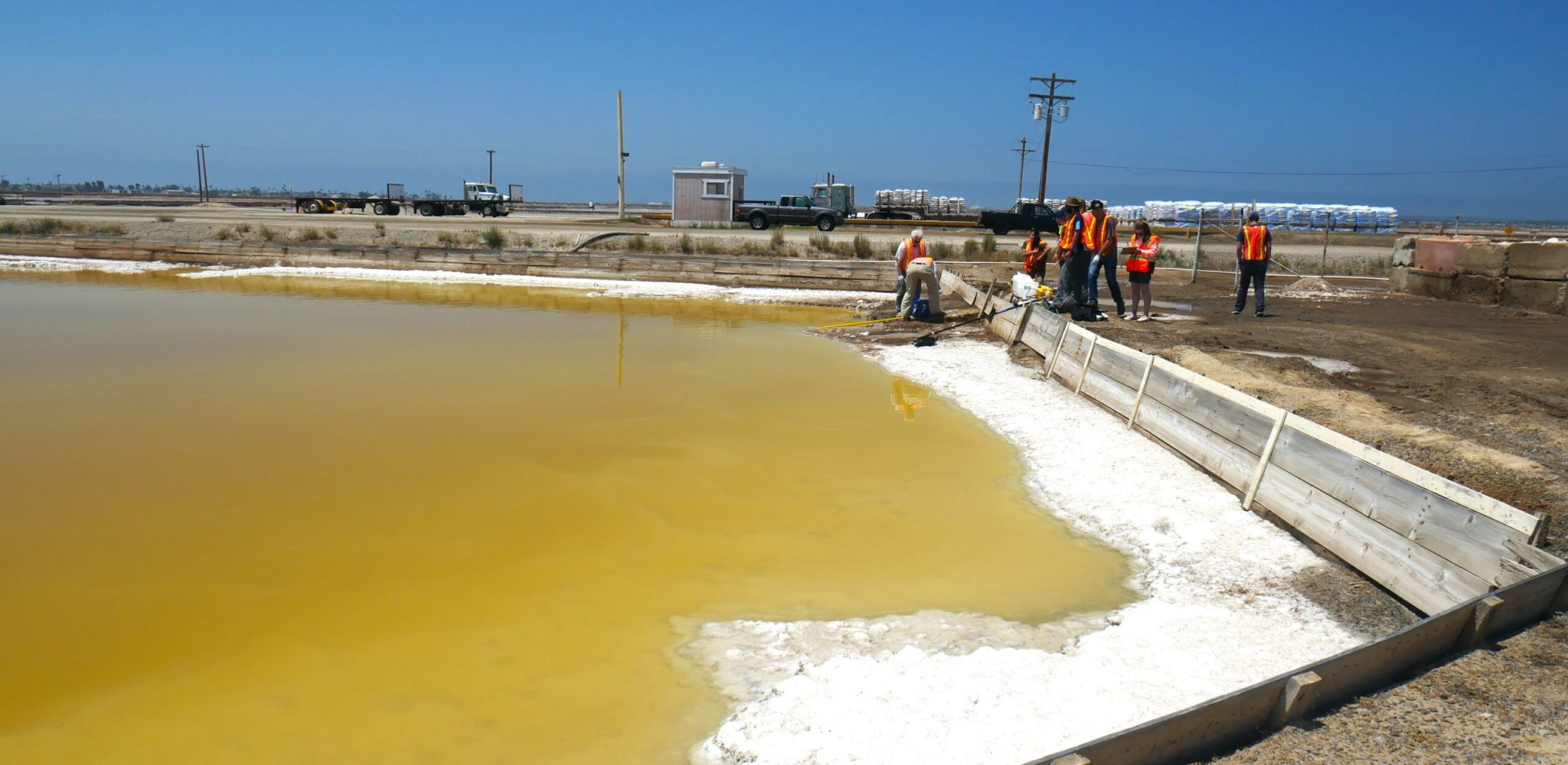 Photo of a yellow-brown magnesium chloride evaporation pool at South Bay Salt Works SBSW during 2019 OAST field work.